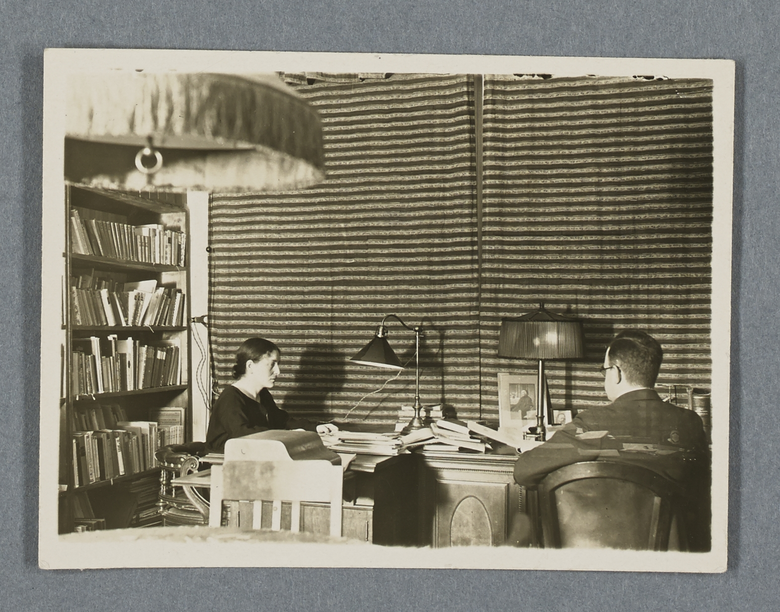 Black and white photo of a man and woman sitting at a writing desk